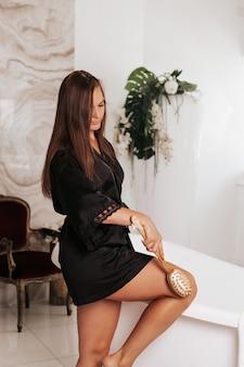 Vrouw de huid van haar benen masseren met een droge massageborstel in de badkamer. het meisje vecht tegen cellulitis