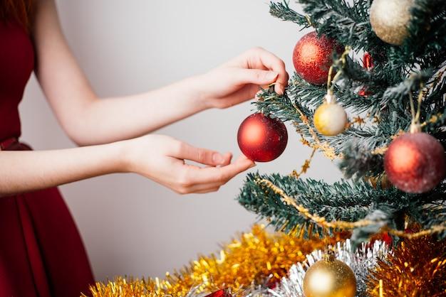 Vrouw de kerstboom versieren met ballen en klatergoud