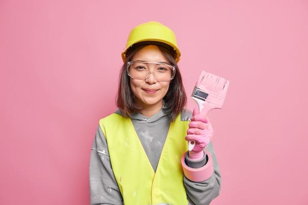 Vrouw decorateur houdt schilderborstel beschermende transparante bril veiligheidshelm renoveert muren op appartement