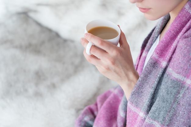 Vrouw deken houden koffiemok warme drank drinken Premium Foto