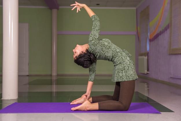 Vrouw demonstreert yogaposities in fitness class./yoga leerling yoga onderwijzen in een studio.
