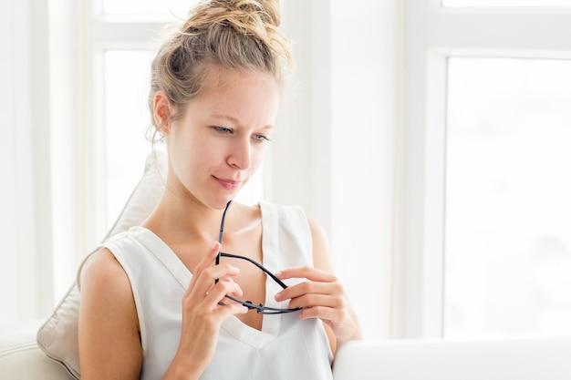 Vrouw denken en werken op laptop in venster