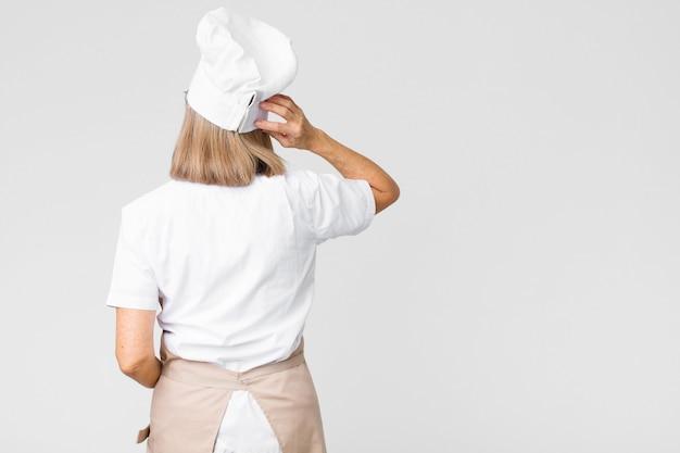 Vrouw denken of twijfelen, hoofd krabben, verward en verward voelen, achter- of achteraanzicht