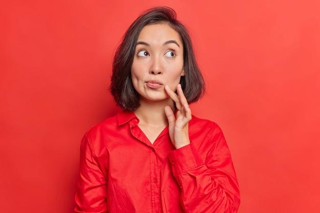 Vrouw denkt na over de toekomst en beslist wat ze gaat kopen terwijl ze boodschappen doet geïsoleerd op rood