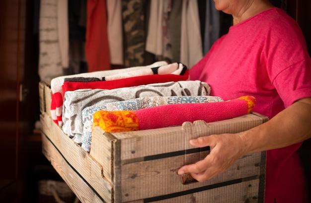 Vrouw des huizes schikt de dekens of plaids in een container om ze te bewaren. assortiment en diverse kleuren