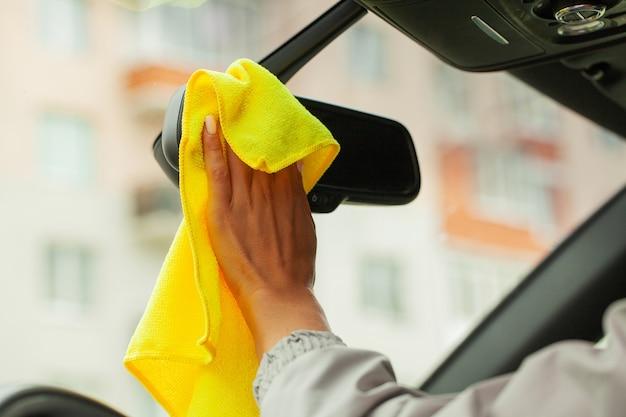 Vrouw desinfecteren en schoonmaken van het interieur van de auto