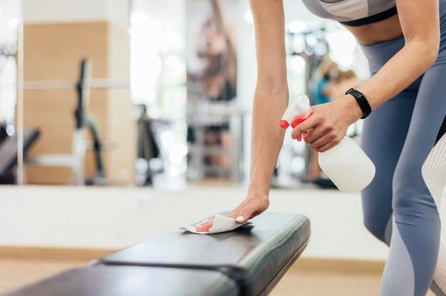 Vrouw desinfecteren fitnessapparatuur tijdens pandemie
