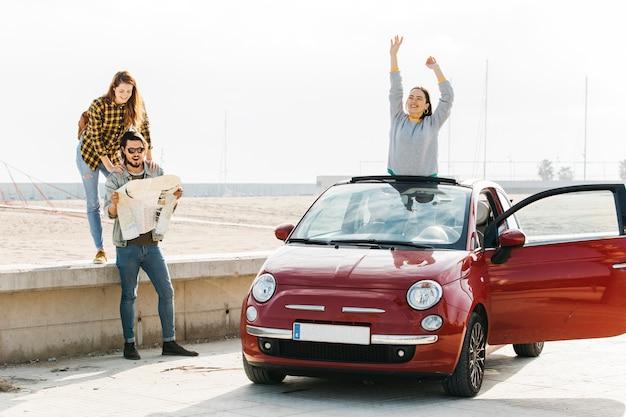 Vrouw dichtbij de mens die kaart en positieve dame bekijken die uit auto dichtbij strand leunen