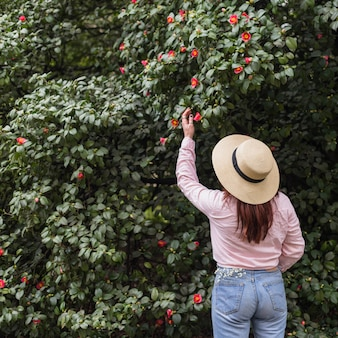 Vrouw dichtbij vele bloemen die op groene takjes groeien