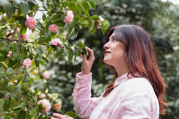 Vrouw dichtbij vele roze bloemen die op groene takjes groeien
