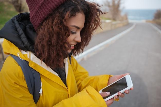 Vrouw dichtbij weg die smartphone gebruiken