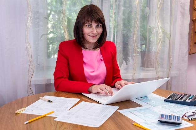 Vrouw die 1040 elektronisch formulier op laptop invult