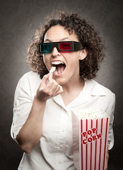 Vrouw die 3d-bril draagt en popcorn eet