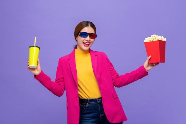 Vrouw die 3d glazen draagt die op film met drank en popcorn letten