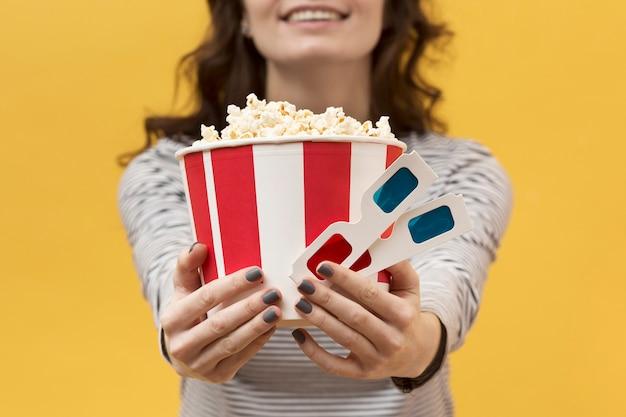 Vrouw die 3d glazen en emmer met popcorn houdt