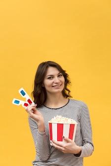 Vrouw die 3d glazen en emmer met popcorn met exemplaarruimte houdt