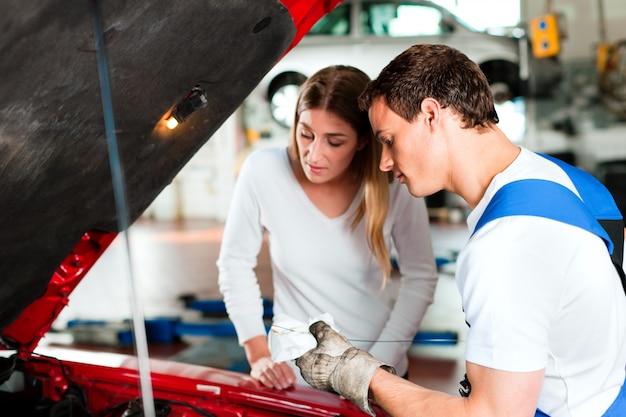 Vrouw die aan automonteur spreekt in reparatiewerkplaats
