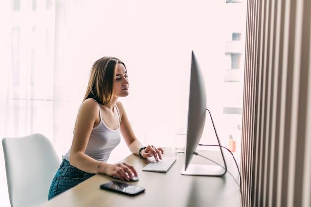 Vrouw die aan computer thuisbureau werkt