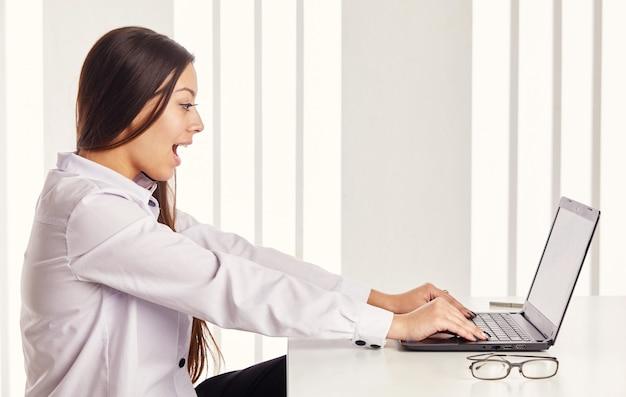 Vrouw die aan computer werkt. meisje opgewonden wat ze ziet op het laptopscherm tijdens het surfen op internet. gezichtsuitdrukking emotie