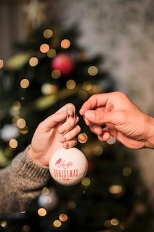 Vrouw die aan de bal van kerstmis van het mensenornament geeft