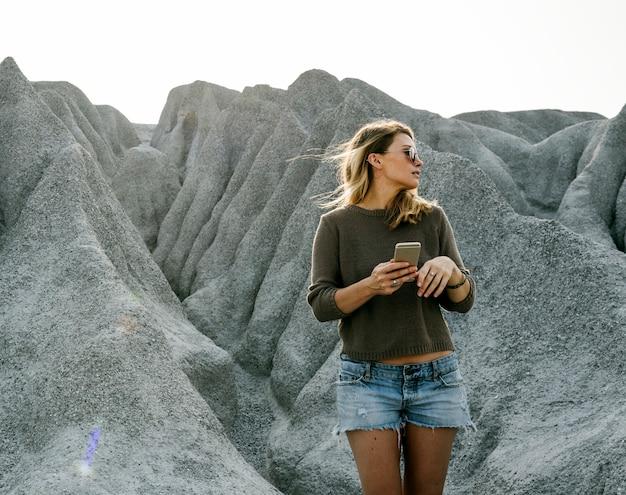 Vrouw die aan de bovenkant van berg in aard wandelt