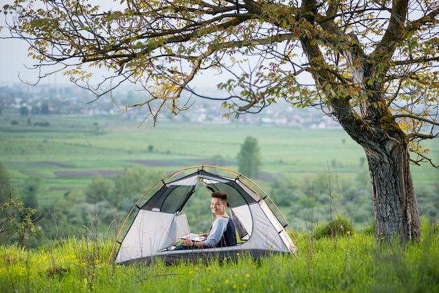 Vrouw die aan de camera glimlachen terwijl in openlucht het gebruiken van haar laptop die in een tent bovenop een heuvel onder boom zitten terwijl het kamperen
