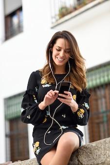 Vrouw die aan de muziek met in openlucht oortelefoons en slimme telefoon luisteren.