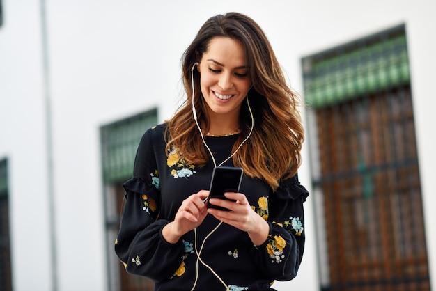 Vrouw die aan de muziek met oortelefoons en slimme telefoon in openlucht luistert.
