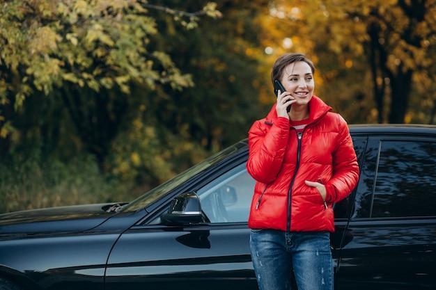 Vrouw die aan de telefoon praat en bij haar auto staat