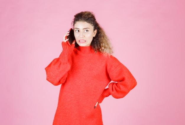 Vrouw die aan de telefoon praat en zich teleurgesteld voelt.