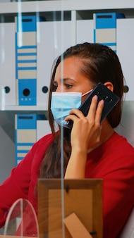 Vrouw die aan de telefoon praat met een medisch gezichtsmasker op kantoor met respect voor sociale afstand. freelancer die op een nieuwe, normale werkplek aan het chatten is met een team op afstand dat op smartphone spreekt
