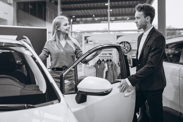 Vrouw die aan de verkoopman spreekt in een autotoonzaal