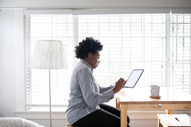 Vrouw die aan een digitale tablet in het nieuwe normaal werkt