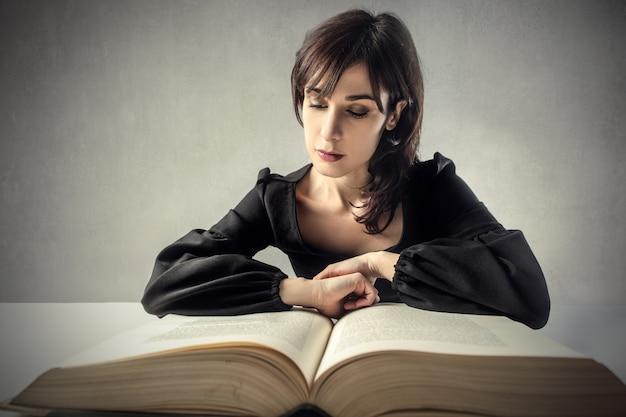 Vrouw die aan een groot boek studeert