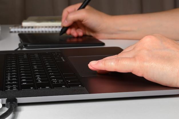 Vrouw die aan een laptop en een grafisch tablet werkt