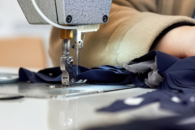 Vrouw die aan een naaimachine werkt met blauwe stof