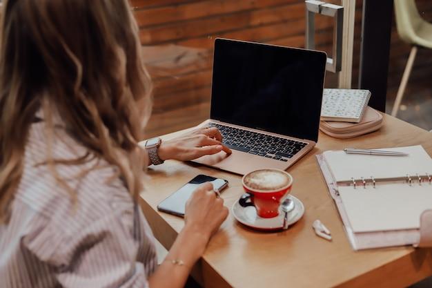Vrouw die aan een notitieboekje in een koffie werkt.