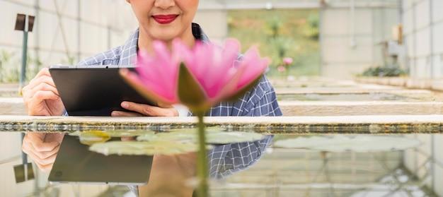 Vrouw die aan een tuinierproject werkt met een tablet