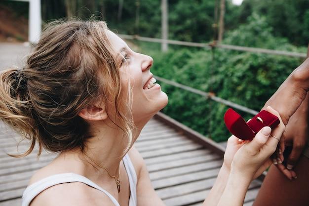 Vrouw die aan haar gelukkige vriendin in openlucht liefde en huwelijksconcept voorstellen
