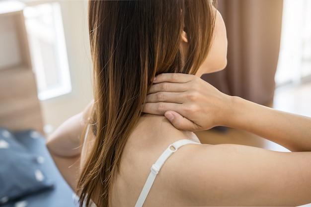Vrouw die aan halspijn op het bed lijden