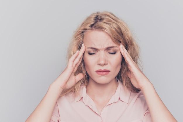 Vrouw die aan hoofdpijn lijdt die op grijs wordt geïsoleerd