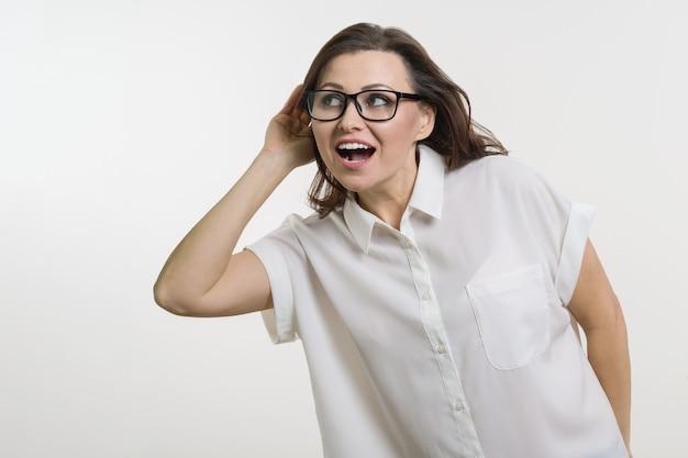 Vrouw die aan iets luistert dat hand houdt dichtbij haar oor.