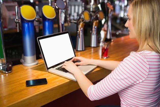 Vrouw die aan laptop bij barteller werkt