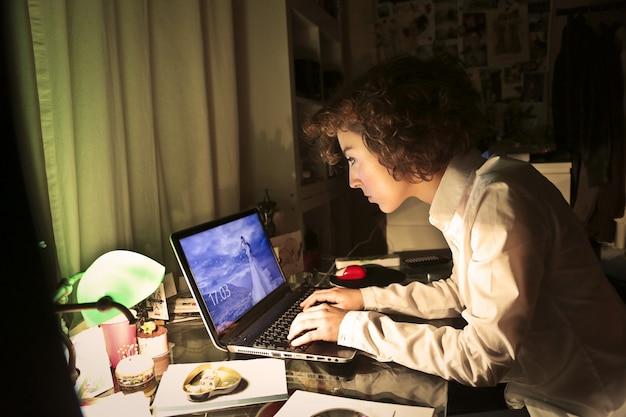 Vrouw die aan laptop bij nacht werkt