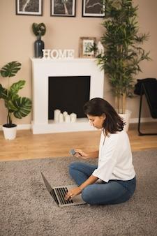 Vrouw die aan laptop in woonkamer werkt