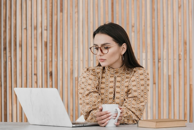 Vrouw die aan laptop middelgroot schot werkt
