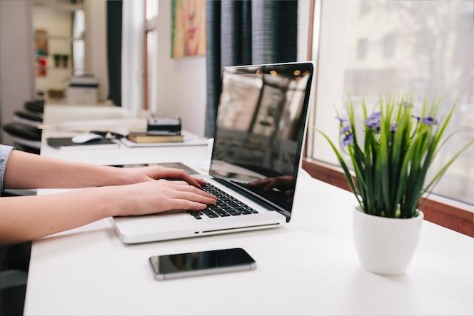 Vrouw die aan laptop op het werk werkt