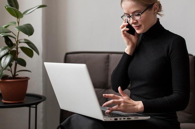 Vrouw die aan laptop werkt en bij telefoon spreekt