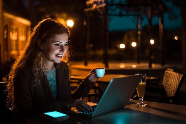 Vrouw die aan laptop werkt en koffie drinkt bij nacht. hoge iso-afbeelding.
