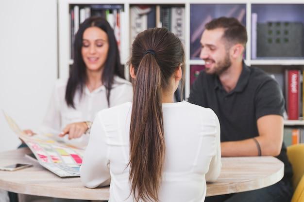 Vrouw die aan mensen in bureau spreekt